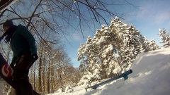 A young man snowboarding through trees and doing a rail slide trick. Stock Footage