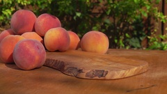 Slices of peaches falling on the wooden table Stock Footage