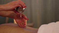Masseuse dripping oil on the back of a patient Stock Footage
