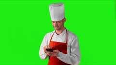 Handsome adult chef typing on smartphone, then he looking at the camera and Stock Footage