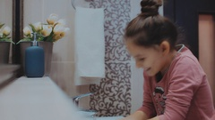 Beautiful young girl washing her face in bath Stock Footage