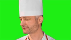 Handsome chef turns head, smiling at the camera and turns back on a green Stock Footage