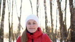 Beautiful young woman in a sunny winter park, playing with snow, having fun Stock Footage