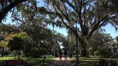 Two tourists walk in Park Avenue Park, Tallahassee, Florida, USA Stock Footage