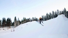 A skier doing a jumping trick on skis in the winter at a ski resort. Stock Footage