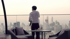Young man taking photo of cityscape standing on terrace in bar Stock Footage
