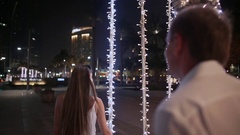 Dubai. UAE. Young man and woman walking among glowing palms trees at night in Stock Footage