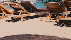 Wooden chair at the beach of background of blue sea Stock Footage