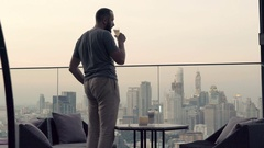 Man drinking cocktail and admire view from terrace in bar in evening Stock Footage
