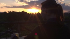 CLOSE UP: Woman watching golden sunset sitting on veranda in glamping lodge Stock Footage