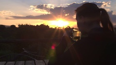 CLOSE UP: Tourist watching golden sunset sitting on terrace in safari lodge Stock Footage