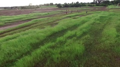 Children run on a green African plain to escape from the drone. Stock Footage