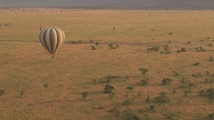 AERIAL: Safari hot air balloon full of happy tourists flying above the ground Stock Footage