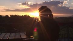 CLOSE UP: Girl drinking tea sitting on safari lodge terrace at golden sunrise Stock Footage