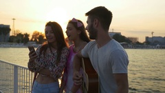 Three friends singing with a guitar on a bridge over the sea on summer time Stock Footage