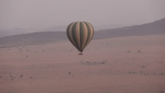 AERIAL: Tourists flying in safari hot air ballon high above the ground at dawn Stock Footage
