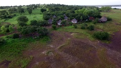 An African village among the trees in a green African plain Stock Footage