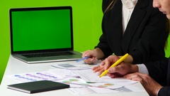 Work desk in the office, man and woman draw a graph, open notebook with green Stock Footage