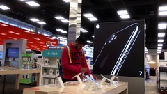 Motion of people playing iphone at Best Buy store with 4k resolution Stock Footage