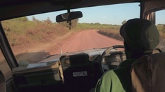FPV: Safari guide in jeep driving past Masai man walking along dusty rocky road Stock Footage