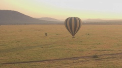 AERIAL: Ballon safari drifting through air close above ground on sunny morning Stock Footage