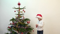 Adorable child with Santa clause cap decorating Christmas tree Stock Footage
