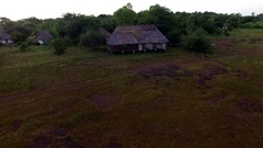 An hut among the trees in a green African plain Aerial video Stock Footage