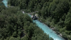 Aerial - Flying over the wooden bridge over beautiful emerald river Stock Footage