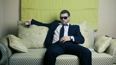 Businessman with a glass of whiskey on the couch Stock Footage