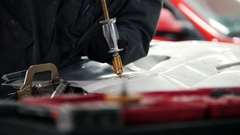 Car service - worker repairing automobile body, close up Stock Footage