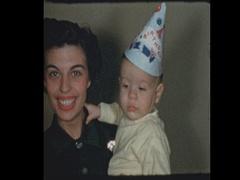 50's Mom lights baby boys 1st birthday cake Stock Footage