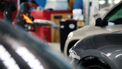 Professional car service - worker manuals circular saw, defocused background Stock Footage