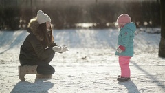 Laughing Woman in Warm Clothing is Throwing Snow at Her Daughter Wearing Stock Footage