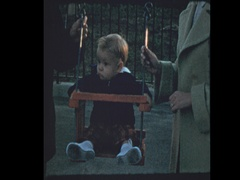 50's family pushes baby in antique wooden swing Stock Footage