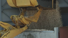 Excavator unloading wood chips into a tank Stock Footage
