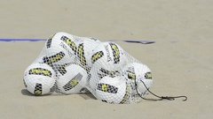 A bag of beach volleyballs being dumped out by a female player. Stock Footage