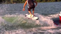 A man skim wakeboarding behind a boat on a lake, slow motion. Stock Footage