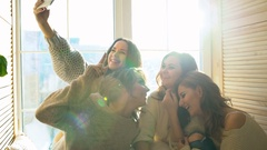 Four beautiful girls shoot selfie sitting on window. Girlfriends having fun and Stock Footage