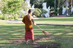 Buddhist monk working with broom sweeps lawn from fallen leaves in temple Stock Photos
