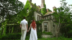 Honeymoon couple looking at beautiful country house. Fairytale house Stock Footage