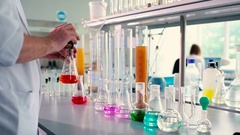 Male adds orange dye in conical flasks. Stock Footage