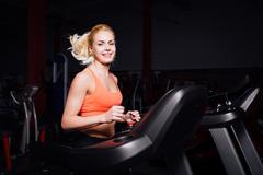 Young beautiful cute girl in fitness model in the gym running on the treadmill Kuvituskuvat