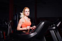 Young beautiful cute girl in fitness model in the gym running on the treadmill Stock Photos