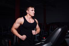 Young strong big man fitness model in the gym running on the treadmill with Kuvituskuvat