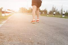 Athletic young man running on road in the park. Healthy lifestyle Stock Photos
