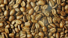 Hot choicest Arabica beans, rotate. Above them, a wisp of smoke Stock Footage