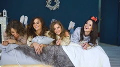 Four beautiful girls lie on bed smiling . Girlfriends having fun and laugh in Stock Footage