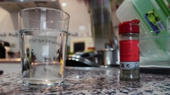 Condiments pour into a glass of water Stock Footage