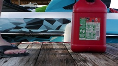 A man fills up his boat with gasoline before wake surfing. Stock Footage