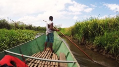 Malagasy man from village on Madagascar river Antainambalana helping ride boat t Stock Footage